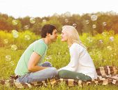 stock photo of have sweet dreams  - Pretty romantic couple in love having fun soap bubbles - JPG