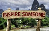 Inspire Someone sign with a forest background