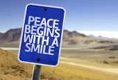 Peace Begins With a Smile sign with a desert background