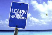 Learn From Yesterday sign with a beach on background