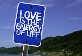 Love is The Energy of Life sign with a beach on background