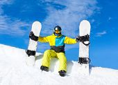 Snowboarder sitting snow slope snowboards
