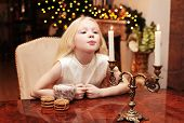 Christmas, Celebration, Holiday, Xmas Concept - Cute Child Blowing On A Candle And Makes A Wish
