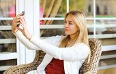 Technology, Mobile And People Concept - Pretty Girl Makes Self-portrait On The Smartphone Outdoors