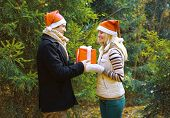 Christmas And People Concept - Man Giving A Box Gift To A Woman, Happy Pretty Couple In Love Against