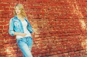 beautiful sexy blonde woman standing near a brick wall in a denim jacket and pants