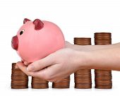 stock photo of coin slot  - Woman hand holding a pink piggy bank on the background coins - JPG