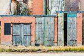 picture of windows doors  - Wooden garage doors of different hights on red brick building - JPG