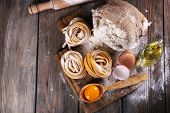 stock photo of ingredient  - Raw homemade pasta and ingredients for pasta on wooden background - JPG