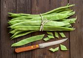 stock photo of phaseolus  - Piattoni green beans with knife on the old wooden table - JPG