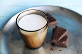 picture of bittersweet  - Glass of milk with chocolate chunks on metal tray and color wooden planks background - JPG