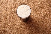 picture of malt  - Nonic pint glass of dark stout beer over malted barley grains - JPG