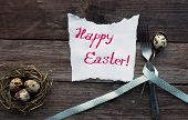 image of quail  - Quail eggs on a rustic wooden table and handwritten Happy Easter message - JPG