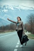 pic of independent woman  - Young woman hitchhiking on countryside road - JPG