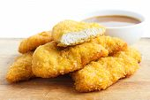 picture of curry chicken  - Golden fried chicken strips on wood board - JPG