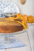 image of sponge-cake  - Homemade orange sponge cake on a glass cake stand over the kitchen table - JPG