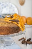 stock photo of sponge-cake  - Homemade orange sponge cake on a glass cake stand over the kitchen table - JPG