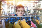 pic of thrift store  - portrait of a teenage boy behind a clothes rail on a flea market