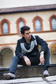 foto of tilt  - Stylish trendy young man sitting outdoor in old historical building looking to a side - JPG