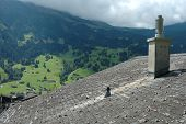 picture of shingles  - Chimney on roof covered with shingles and cloudy mountain view - JPG