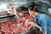 image of slaughterhouse  - Mid adult woman buying fresh red meat in butchery - JPG