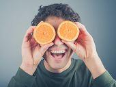 pic of binoculars  - A silly young man is pretending to use two orange halves as binoculars - JPG