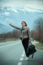 picture of independent woman  - Young woman hitchhiking on countryside road - JPG