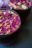 foto of rose bud  - Rose bud tea in the vintage spoons on the black stone desk - JPG