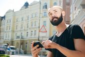 picture of cartographer  - Handsome hipster guy is holding navigator in his hands and looking aside - JPG