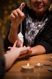 pic of pendulum  - Close up of female fortune teller using pendulum during seance - JPG