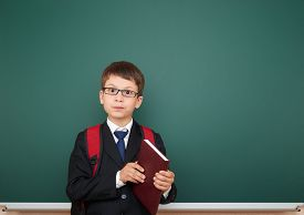 pic of schoolboys  - Schoolboy with backpack on school board background - JPG