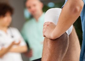 picture of physiotherapist  - Physiotherapist training with patient and doctors in background - JPG