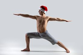 picture of virabhadrasana  - Sporty muscular young man in red Santa Claus Christmas hat working out yoga pilates fitness training doing lunge exercise Warrior II posture Virabhadrasana 2 - JPG