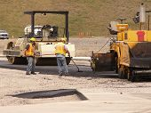 pic of road construction  - Road paving workers laying asphault with steam rollers at construction site.