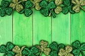 St Patricks Day Double Border Of Shiny Glitter Shamrocks Over A Green Wood Background poster