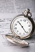 Pocket watch on newspaper about finance