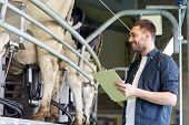 agriculture industry, farming, people, milking and animal husbandry concept - young man or farmer wi poster