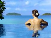 Woman  in the swimming pool near the ocean