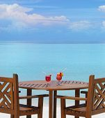 table and chairs on the beach with two red cocktails