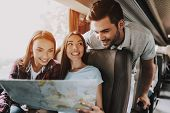 Group Of Young Smiling People Holding Paper Map. Casualy Dressed Happy Travelers Planning Route Toge poster
