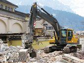 Excavator demolishing an old building