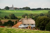 Thatched Roof Cottage And Church Steeple In West Sussex, England