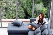 Asian Woman Sit On Sofa Use Smartphone Near Big Glass Windows, Relaxing Alone In House With Green Fo poster
