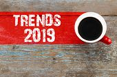 Trends 2019 / Cup Of Coffee With Trends Inscription On Wooden Background. poster