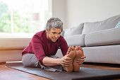 Beautiful senior woman doing stretching exercise while sitting on yoga mat at home. Mature woman exe poster