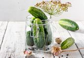 Preserved Cucumbers In Glass Jars With Dill, Pepper And Garlic On Wooden Table poster