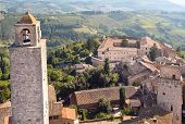 Bell Tower On Cityscape Of San Gimignano, Tuscany Town With Brick Towers And Old Houses. Italian Pro poster