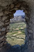 aerial landscaped through a hole in the wall from Acrocorinth a monolithic rock overseeing the ancient city of Corinth, Greece