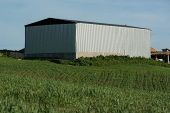 modern building for storage the fodder or the agricultural equipment in a green meadow