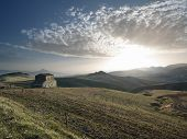the sun is setting on the countryside with abandoned farmhouse in the sicilian hinterland